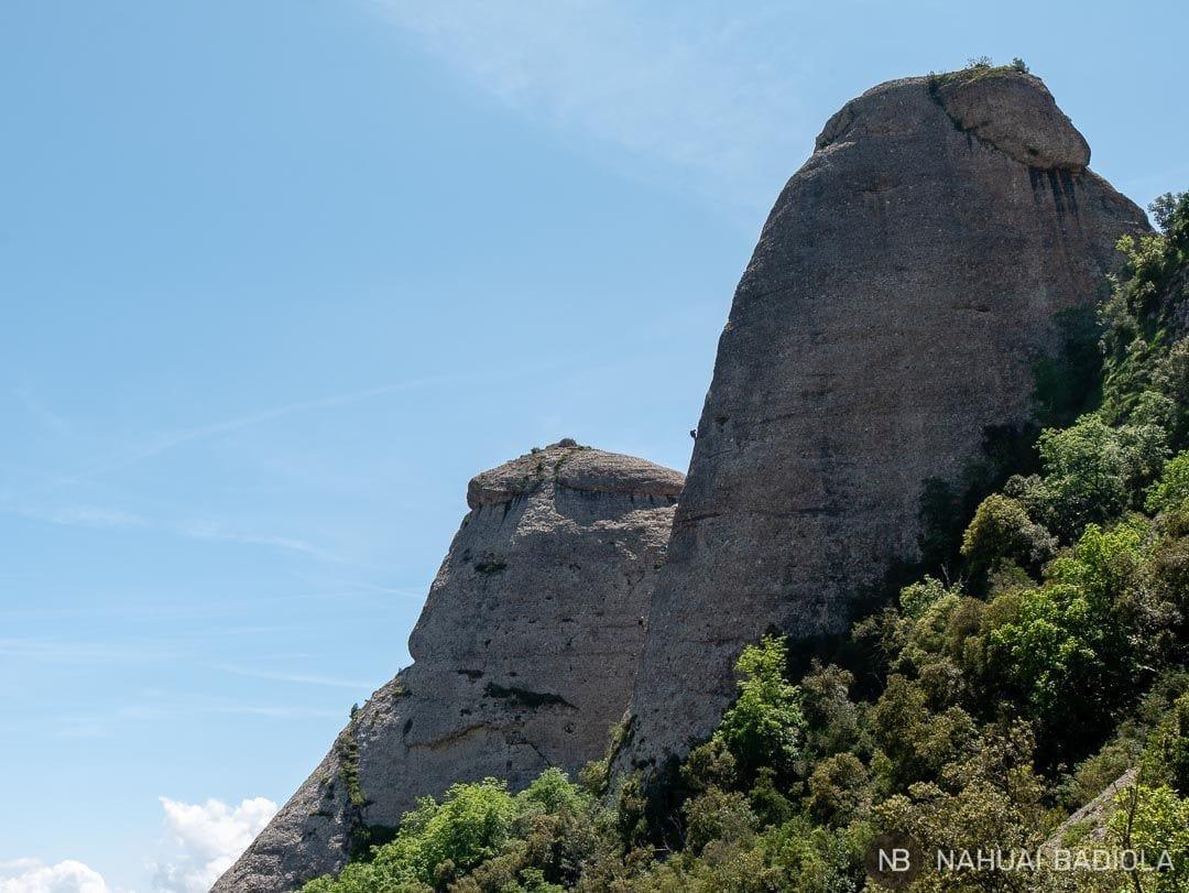 Escalaradores recortados sobre una aguja de Montserrat, Cataluña.