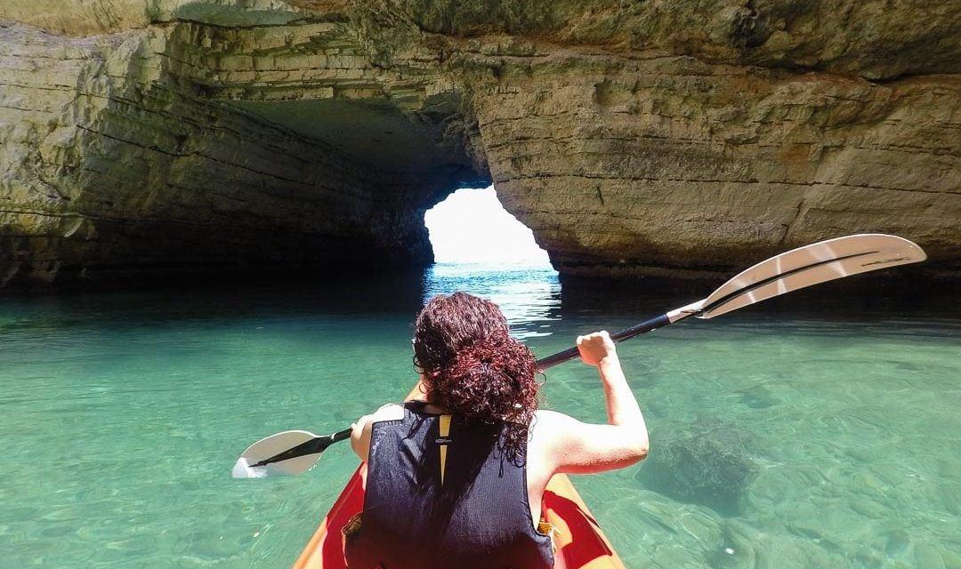 Salida en kayak de una gruta abierta en la costa del Gargano, Italia.