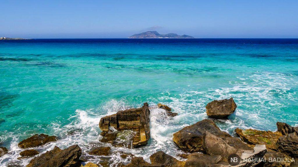 Olas rompiendo en Cala Rossa con la isla Levanzo al fondo.
