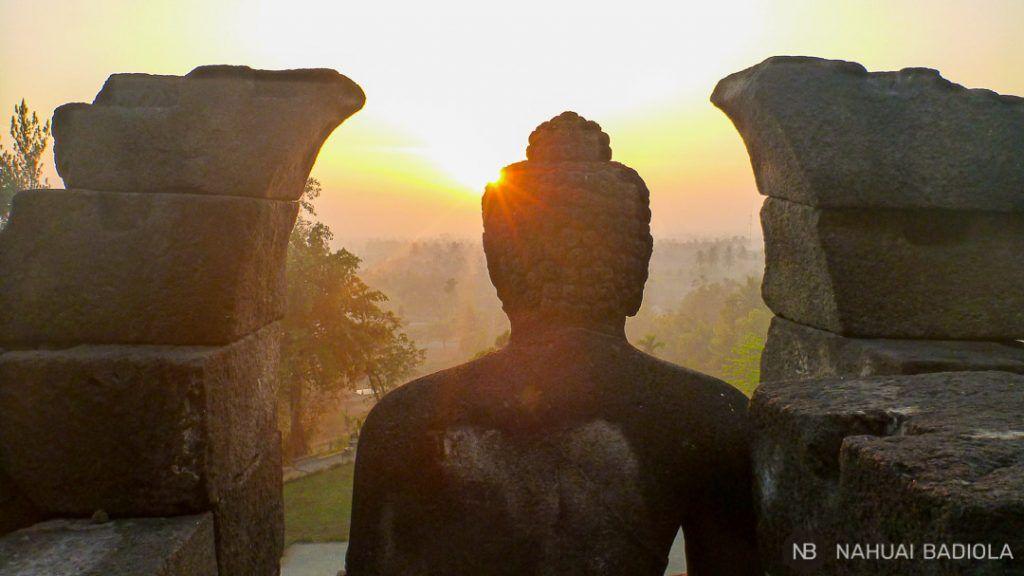 Amanece sobre una de las estatuas del templo Borobudur, Java.