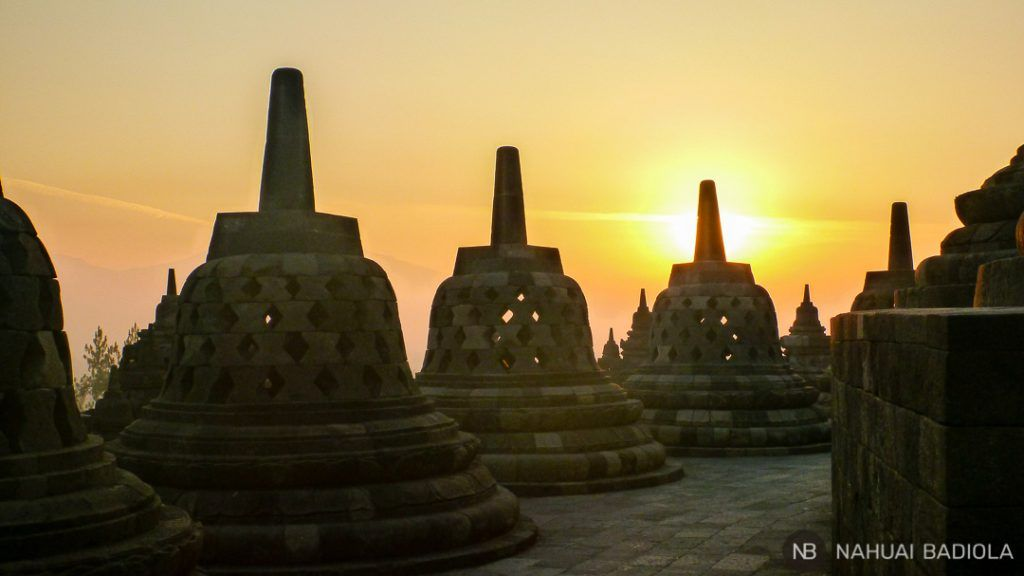 Amanecer sobre las estructuras de campana en el templo de Borobudur, Indonesia.