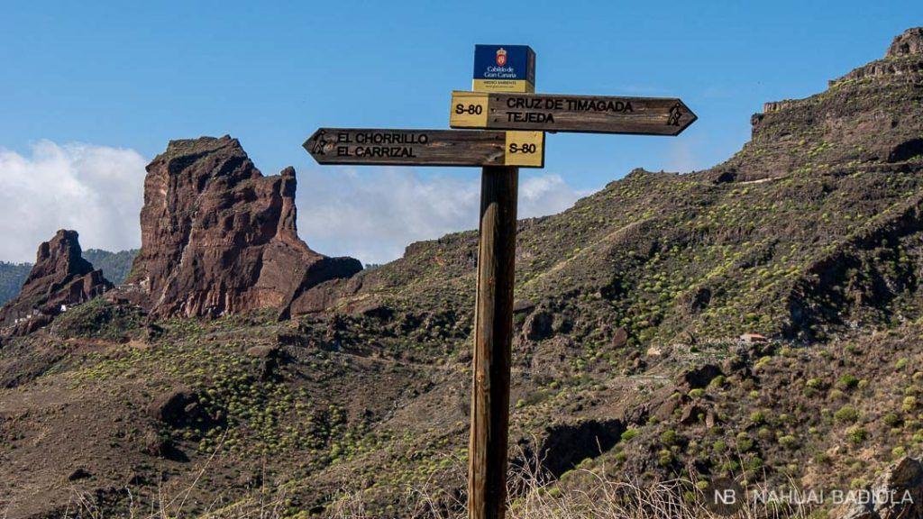 Indicaciones del sendero a Tejeda con las cuevas del Rey detrás
