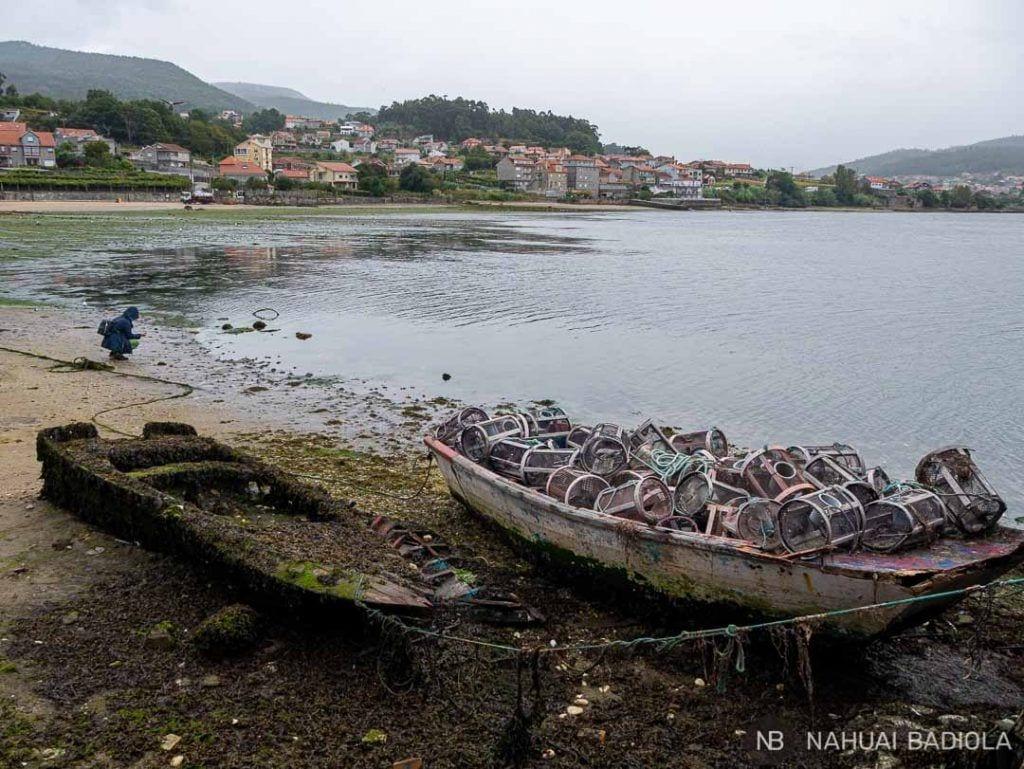 Nasas de pulpo apiladas sobre una vieja embarcación en la playa de Combarro