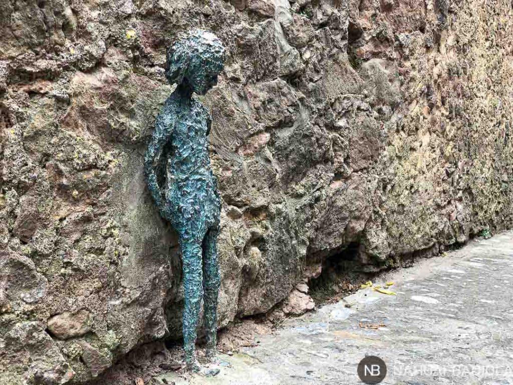 Pequeña escultura de metal con forma de niña en Santa Pau