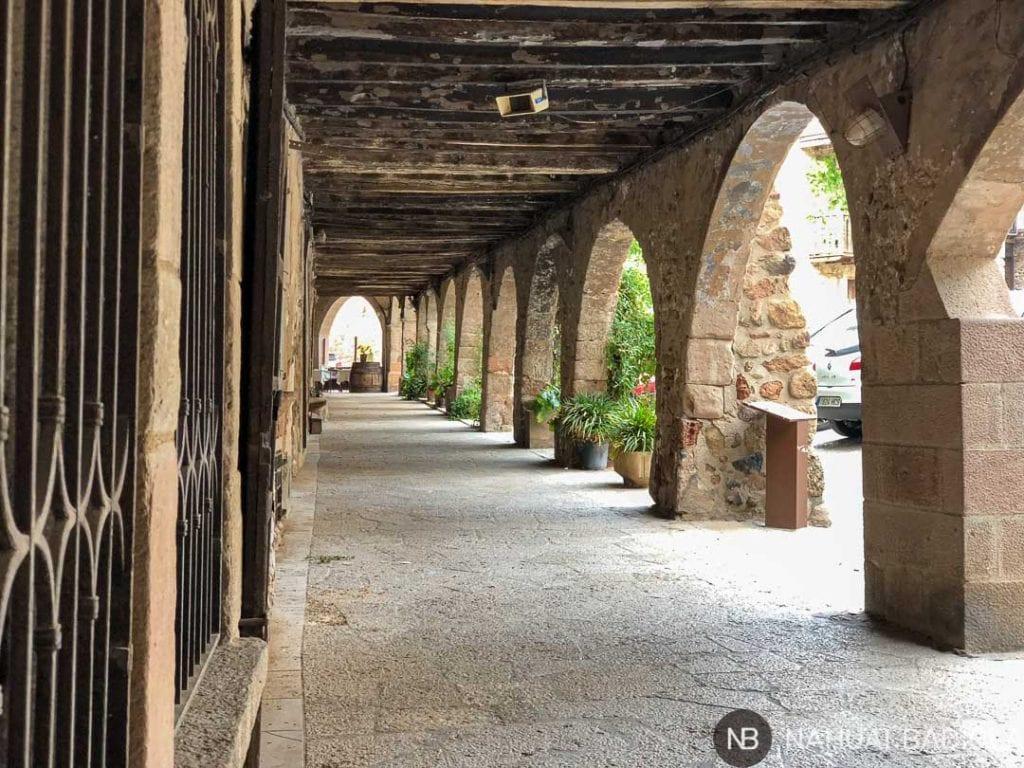 Soportales de piedra en la plaza principal de Santa Pau